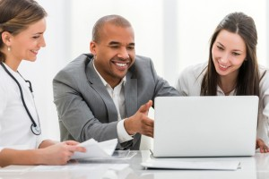 Two happy female doctors and African American businessman working together. They are using computer at doctor's office.